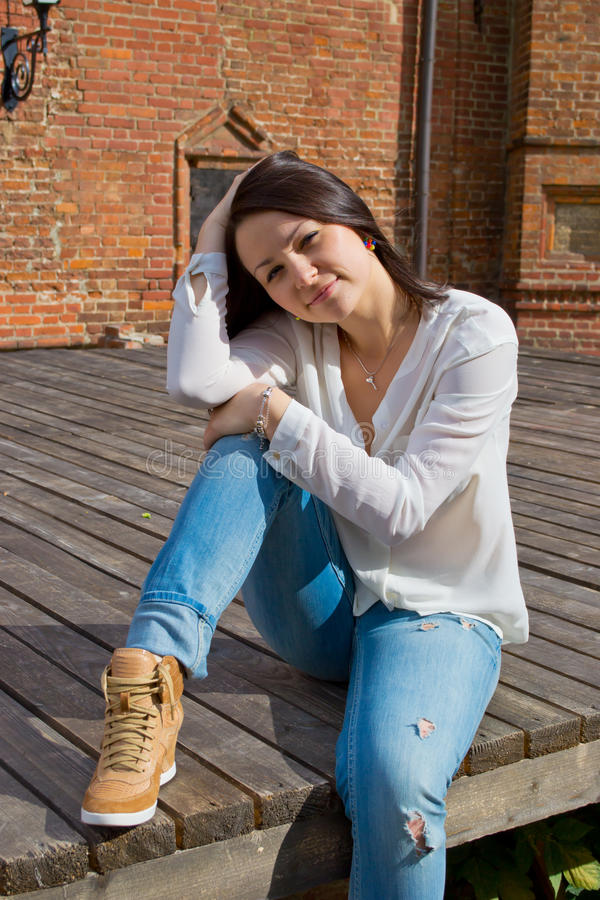 Girl in white blouse. Sitting on the dais with boards royalty free stock photography