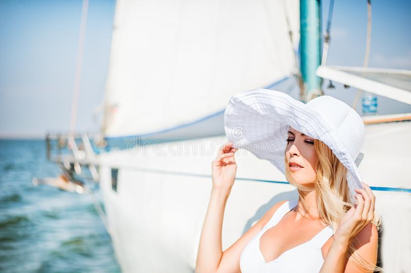 Girl in white broad-brimmed hat near sailing yacht royalty free stock photography