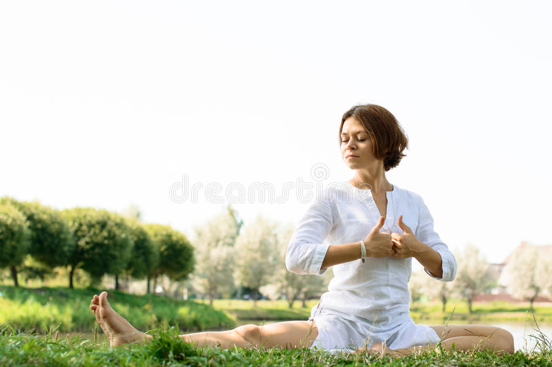 Girl in white clothes practicing yoga at the river-bank royalty free stock photos