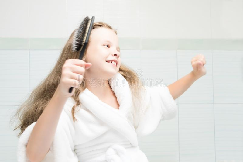 Girl in a white coat dancing in the bathroom and combing her hair stock image