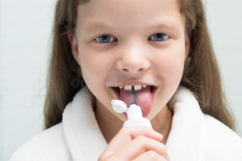 Girl in a white coat eats toothpaste from a white tube, front view stock photography