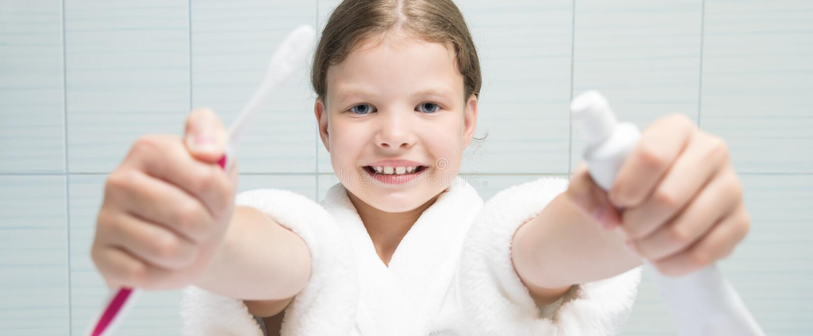 A girl in a white coat holding a toothbrush and toothpaste in her hands, stretching them forward. A girl in a white coat holding a toothbrush and toothpaste in royalty free stock photos