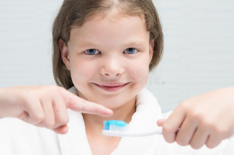 Girl in a white coat holds a brush with toothpaste and points a finger at it stock image