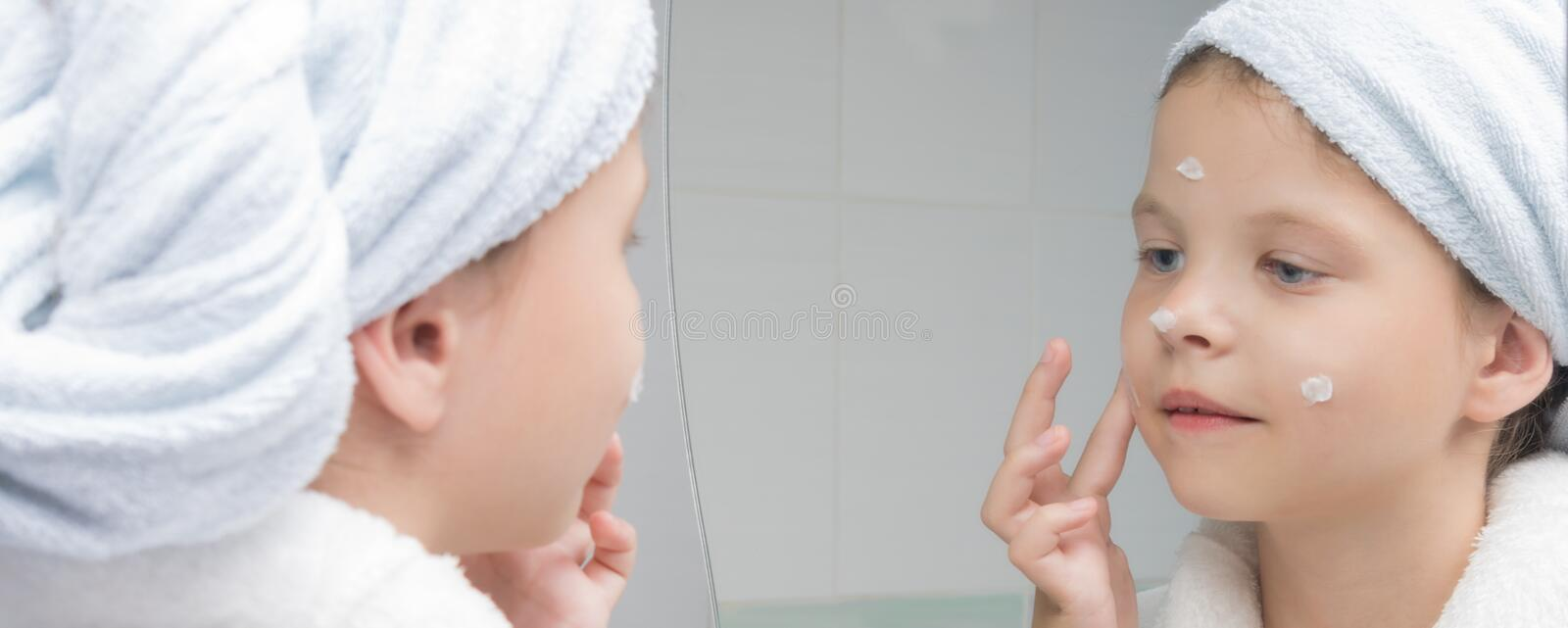 Girl in a white coat with a towel on her head moisturizes face with a cream in front of a mirror. Girl in a white coat with a towel on her head moisturizes face royalty free stock images