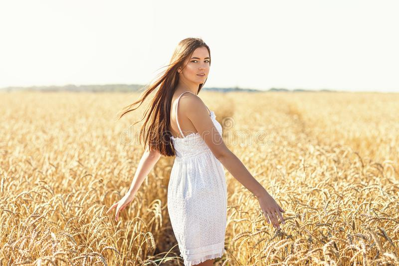 Girl in a white dress on a background of a field with ripe wheat. Model posing on a warm summer morning royalty free stock photography