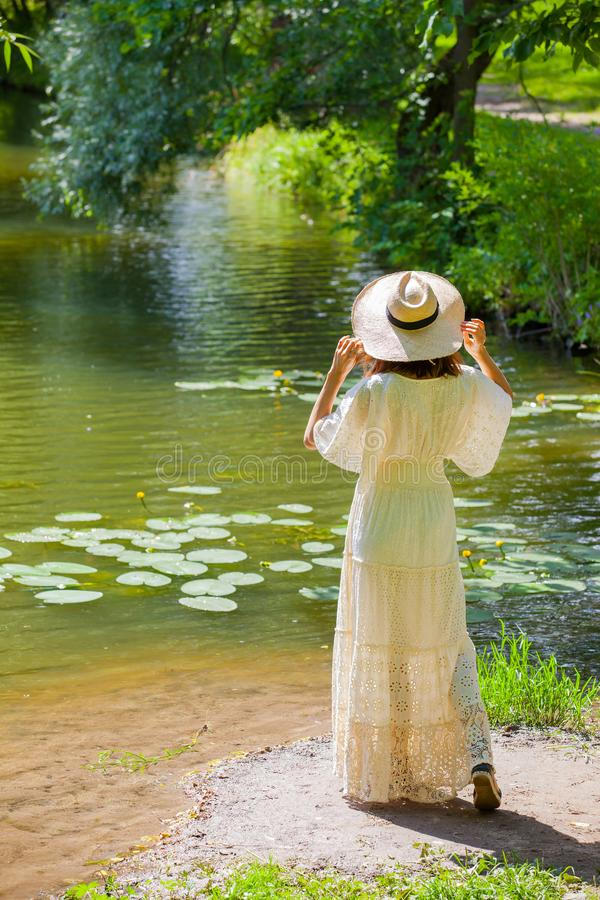 Girl in a white dress and hat on the shore of a pond with water-lilies. Fashion. girl in a white dress and hat on the shore of a pond with water-lilies, sunny royalty free stock photos