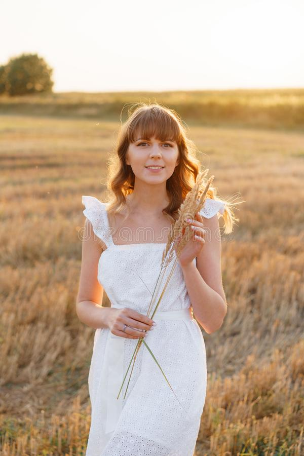 Girl in white dress with spikelets. Woman in field, place for text. Spike and girl in field. Late summer and early stock photos