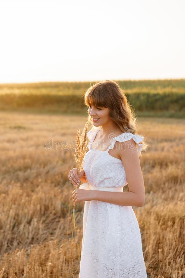 Girl in white dress with spikelets. Woman in field, place for text. Spike and girl in field. Late summer and early royalty free stock images