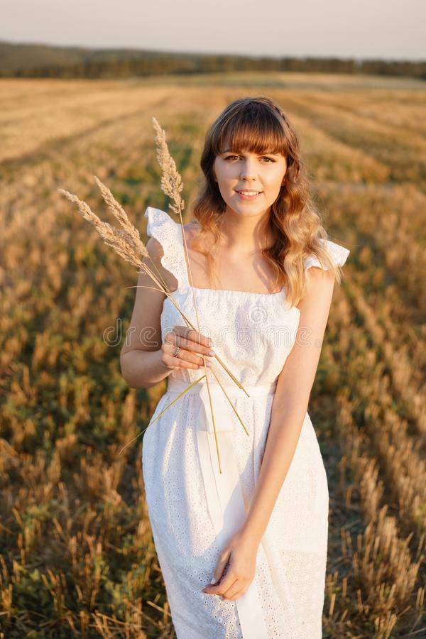 Girl in white dress with spikelets. Woman in field, place for text. Spike and girl in field. Late summer and early royalty free stock photo