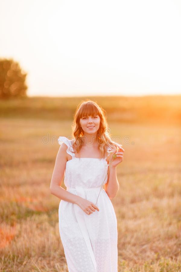 Girl in white dress with spikelets. Woman in field, place for text. Spike and girl in field. Late summer and early stock images