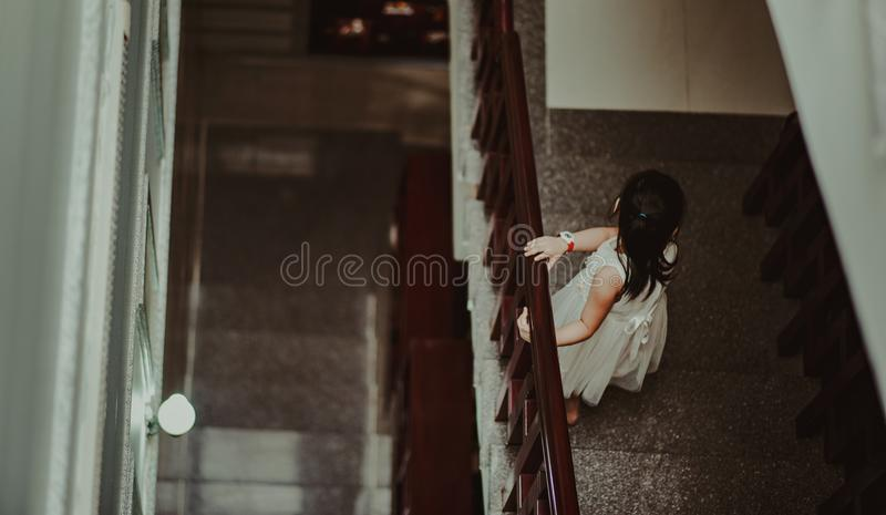 Girl in White Dress Standing in Front of Railings royalty free stock photo
