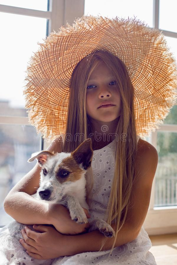 Girl in a white dress and a straw hat sitting on the windowsill stock photo