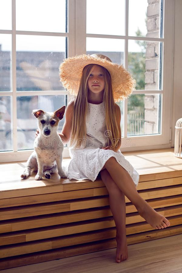 Girl in a white dress and a straw hat sitting on the windowsill stock images