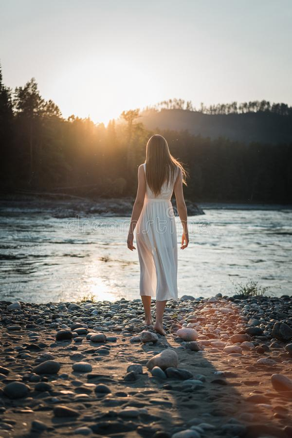 A girl in a white dress is walking along the river bank in the background of mountains and forests stock images