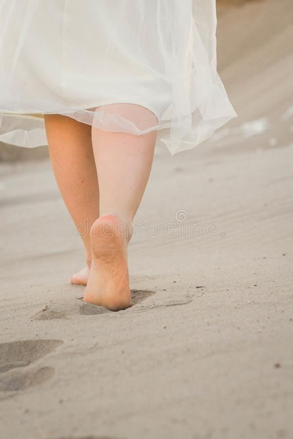 A girl in a white dress walking in the sand royalty free stock photography