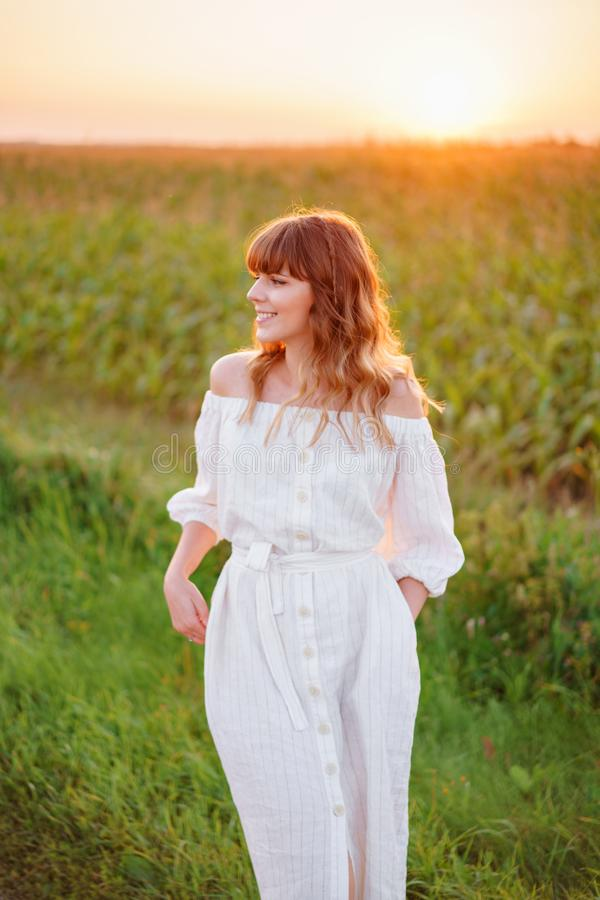 Girl in white dress . Woman in cornfield, place for text. Spike and girl in field. Late summer and early autumn. August. Girl in white dress with spikelets stock photos