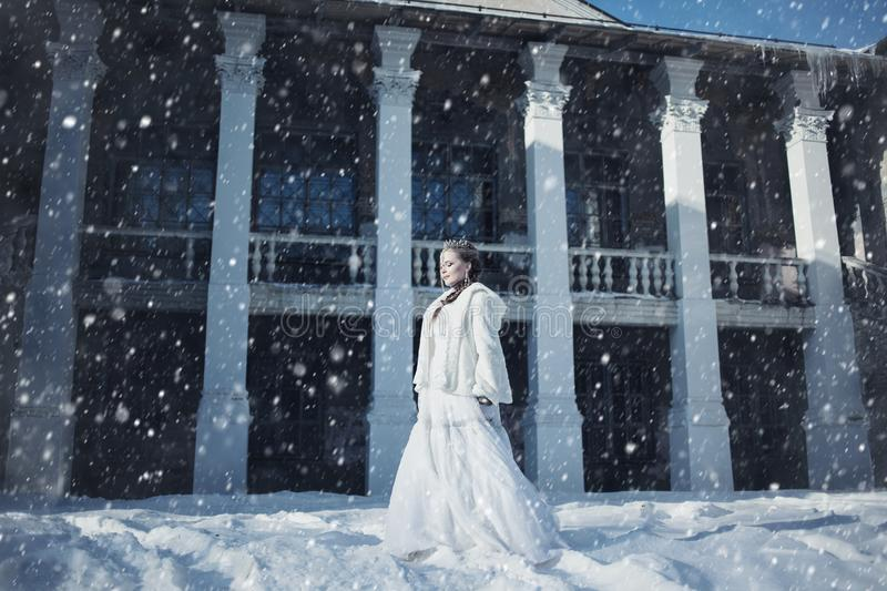 A girl in a white fur coat and crown against the background of an old building royalty free stock images