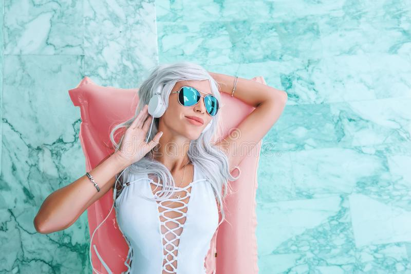 Girl with white hair in headphones listening to music on pink pool float stock photography