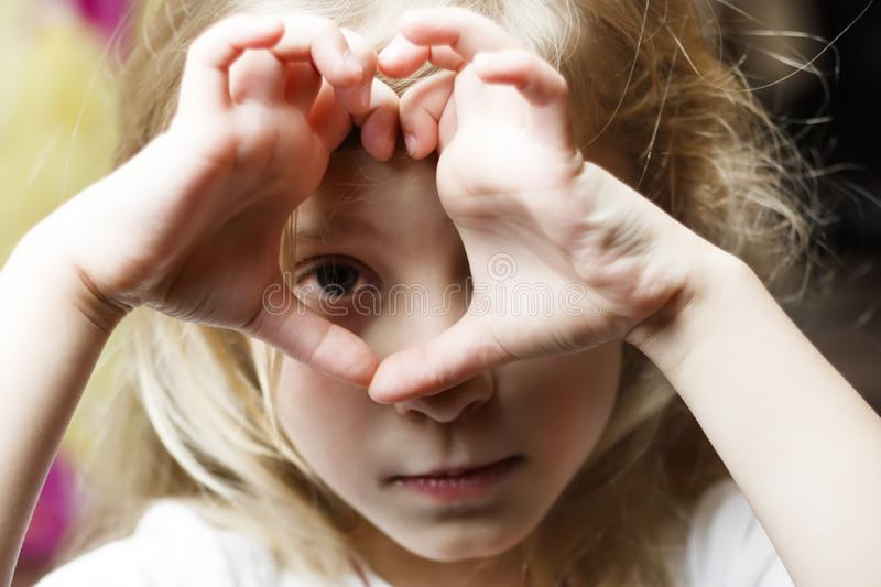 . a girl with white hair makes a heart and looks into it. Concept view in childhood. there is toning. A girl with white hair makes a heart and looks into it stock image