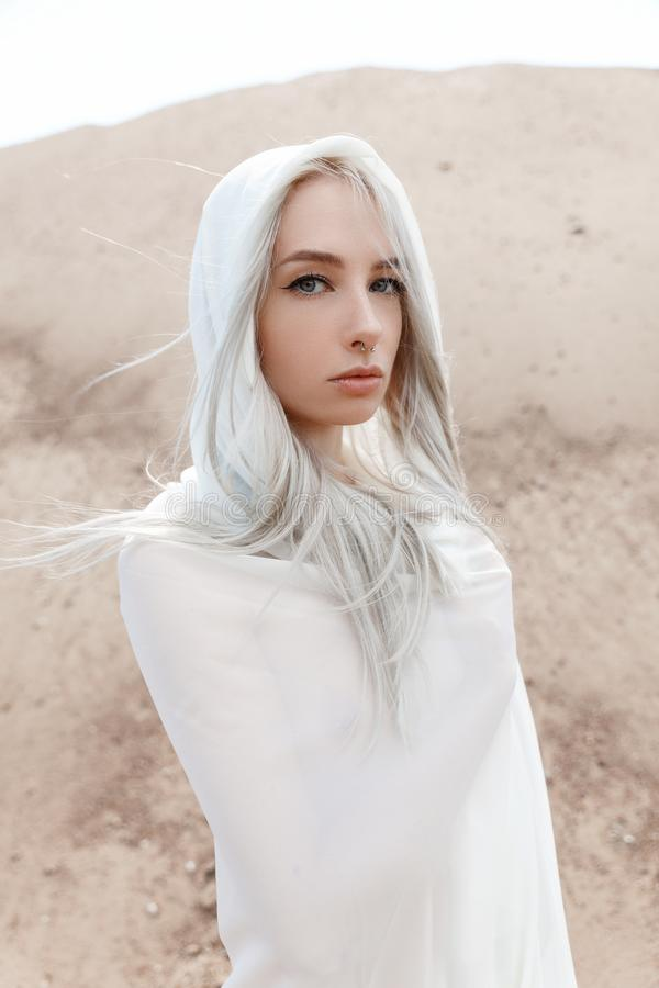 The girl with white hair among the sand mountains stock photo