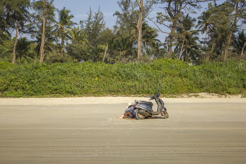 Girl in a white hat sitting by a motorbike on the white sand against the royalty free stock photography