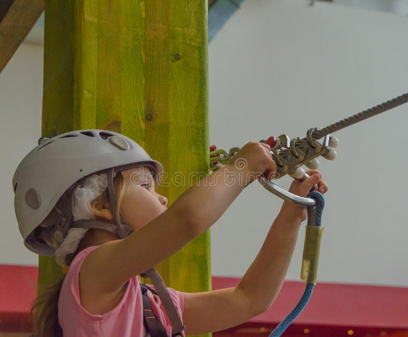Catchy insurance, the adventure Park the kid in the white helmet. The girl in the white helmet in the adventure Park, touches the rifle royalty free stock photography