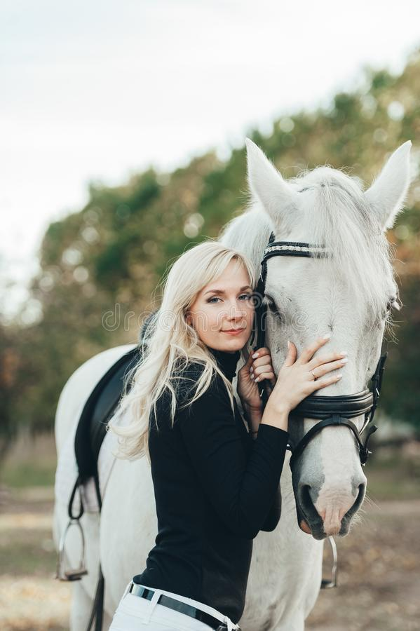 Girl with a white horse. Blonde woman in a ranch stock photo
