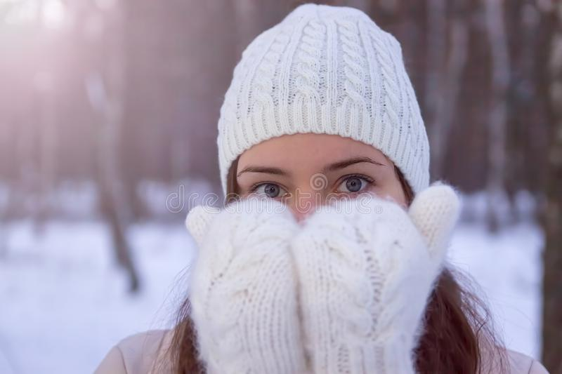 A girl in white knitted mittens and a hat. Snowy forest in the background. Winter. Snow around. A girl in white knitted mittens and a hat. Snowy forest in the stock image
