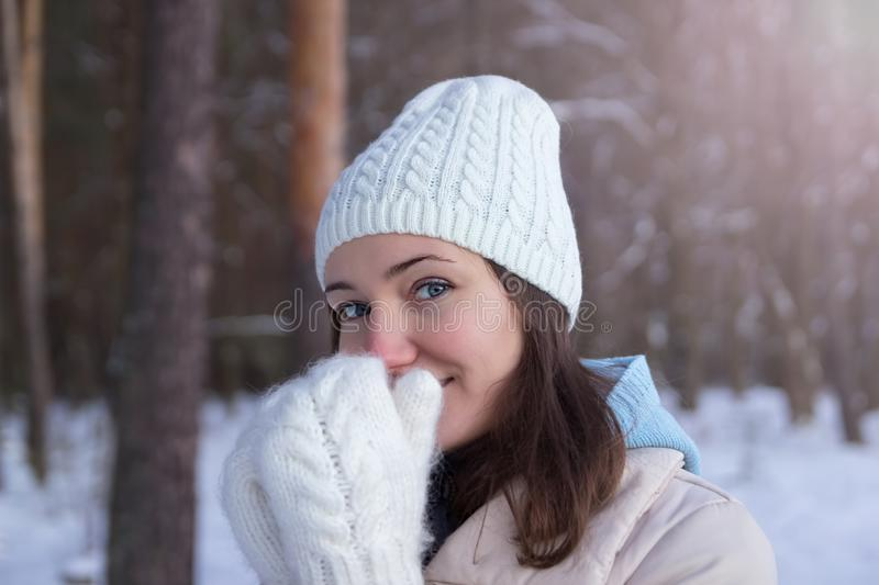 A girl in white knitted mittens and a hat. Snowy forest in the background. Winter. Snow around. A girl in white knitted mittens and a hat. Snowy forest in the royalty free stock images