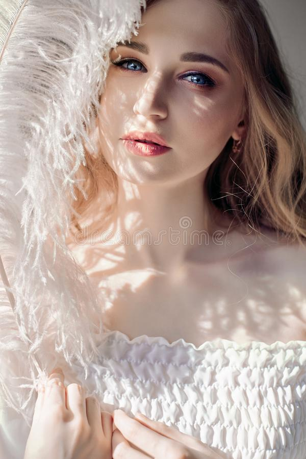 Girl in white light dress and curly hair with big feather near her face, portrait woman with feather, purity and innocence. Curly. Blonde looks romantic stock photo