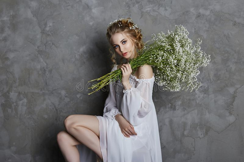 Girl white light dress and curly hair, portrait of woman with flowers at home near the window, purity and innocence. Curly blonde. Romantic look, beautiful eyes royalty free stock image