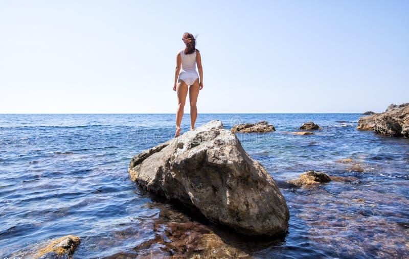 Girl in white lingerie posing back on rock royalty free stock image