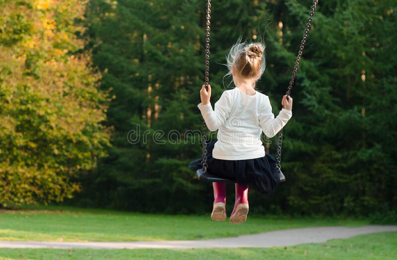 Girl in White Long Sleeve Shirt and Black Skirt Sitting on Swing during Day Time stock image