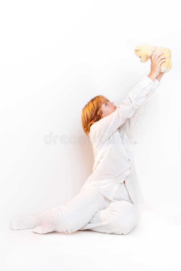 Girl In White Looking At Teddy Bear Stock Images