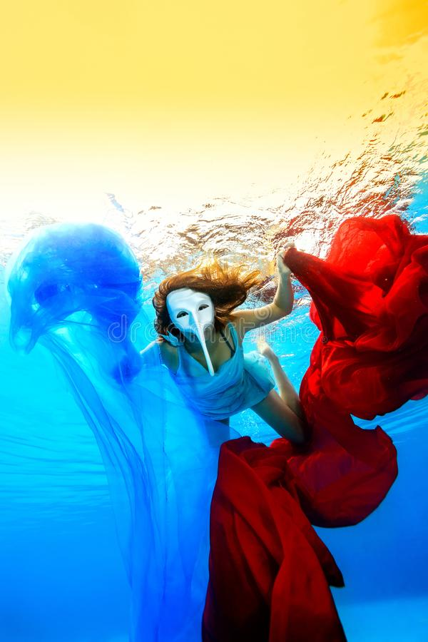 The girl in the white mask swims underwater and plays with red and blue cloth on a background of sunset. royalty free stock photography