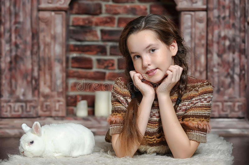 Girl with white rabbit. Young teenage girl with the rabbit stock image