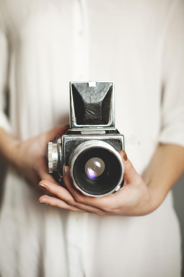 The girl in the white shirt holds a beautiful vintage retro camera. Close up stock photography