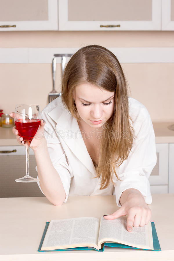 Girl white shirt in the kitchen holding glass and reading a book. Girl in a white shirt in the kitchen holding a glass and reading a book stock photo