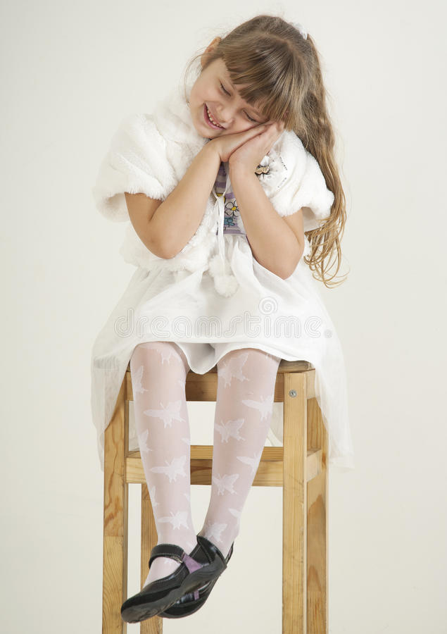 Girl on white sit on chair royalty free stock images