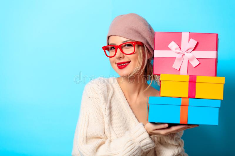 Girl in white sweater with gift colored boxes royalty free stock photo