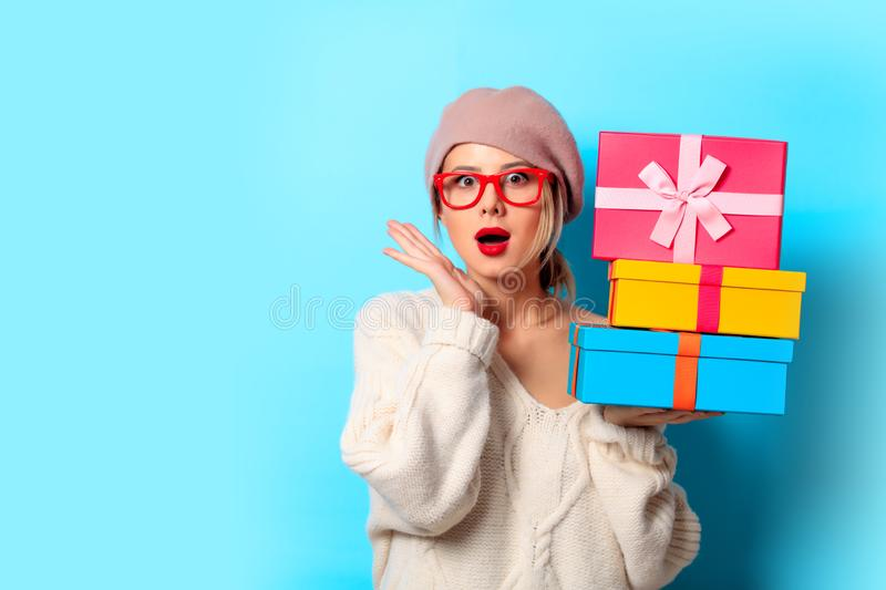 Girl in white sweater with gift colored boxes stock images