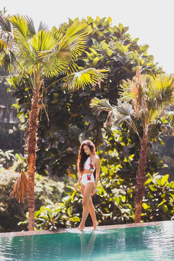 Girl in white swimsuit walking edge infinity pool. Young tanned girl in white swimsuit walking on edge of infinity pool with jungle view in Bali stock image