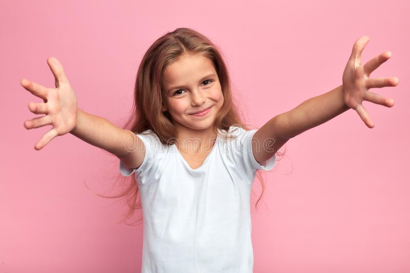 Girl in white t-shirt with arms wide open going to hug her family,. Cheerful positive beautiful girl in white t-shirt with arms wide open looking at the camera stock photography