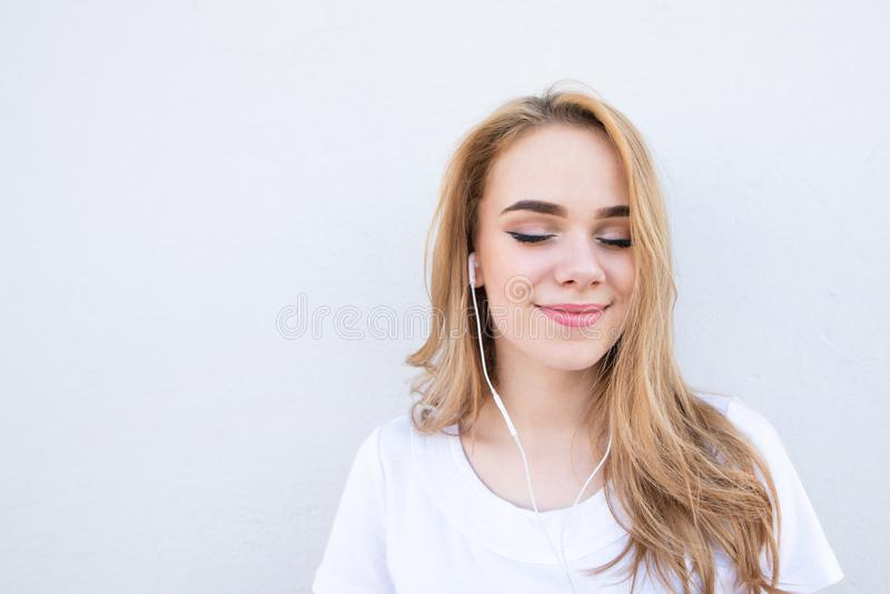 Girl in a white T-shirt, listens to music in her headphones with her eyes closed and smiles on a white background stock photo