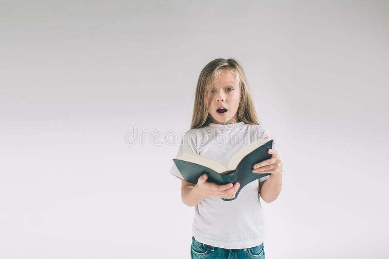 Girl in white t-shirt is reading a book on a white background. Child likes to read books royalty free stock photos