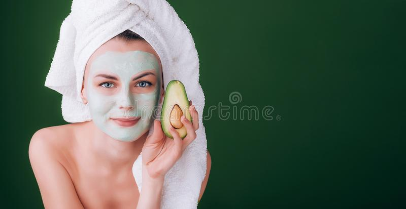Girl with a white towel on her head with a nutritious green mask on her face and an avocado in her hands on a green background wit stock photo