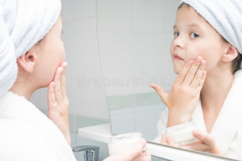A girl with a white towel on her head stands in the bathroom in front of the mirror and smears her face with cream stock image
