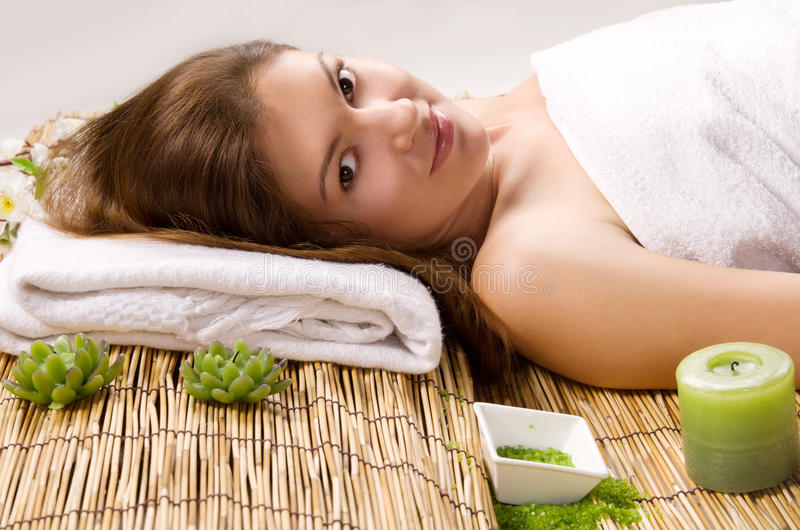Girl in a white towel lying on spa treatments royalty free stock photos