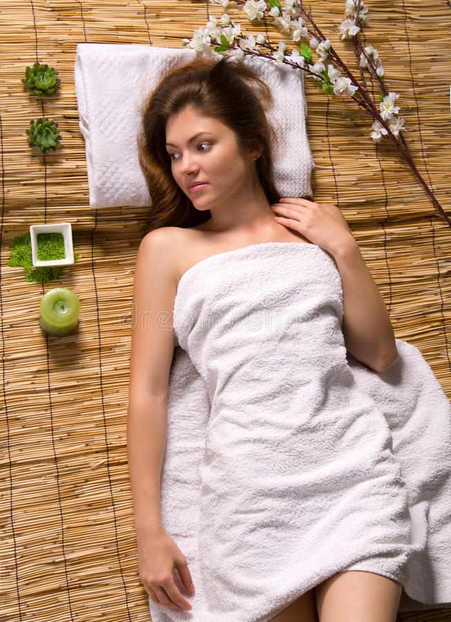 Girl in a white towel lying on spa treatments royalty free stock photo