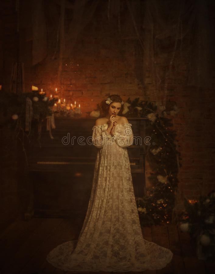 A girl in a white vintage dress with open shoulders stands against the background of an old piano and candles. Gothic. A tender girl in a white vintage dress royalty free stock photography